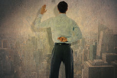 Composite image of businessman crossing fingers behind his back. Businessman crossing fingers behind his back against city skyline Royalty Free Stock Image
