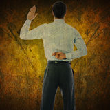 Composite image of businessman crossing fingers behind his back. Businessman crossing fingers behind his back against dark background Royalty Free Stock Photography