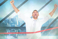 Composite image of businessman crossing the finish line Stock Images