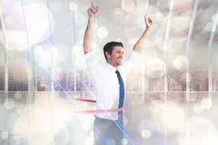 Composite image of businessman crossing the finish line Stock Image
