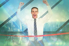 Composite image of businessman crossing the finish line and cheering Stock Images