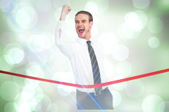 Composite image of businessman crossing the finish line while clenching fist Stock Image