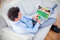 Composite image of businessman doing online shopping on couch royalty free stock photos