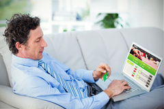 Composite image of businessman doing online shopping on couch Stock Photography