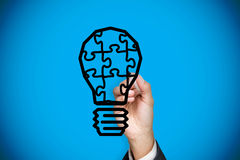 Composite image of businessman drawing light bulb Royalty Free Stock Photos