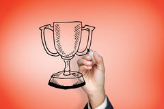 Composite image of businessman drawing winners cup Stock Images