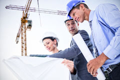 Composite image of businessman explaining a blueprint to his colleagues Royalty Free Stock Photos