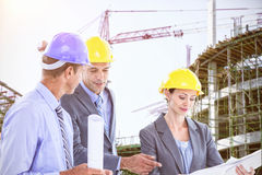 Composite image of businessman explaining a blueprint to his colleagues Royalty Free Stock Image