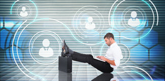 Composite image of businessman with feet up on briefcase Stock Images
