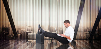 Composite image of businessman with feet up on briefcase Stock Photography
