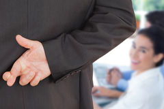 Composite image of businessman with fingers crossed Stock Photos
