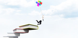 Composite image of businessman flying with balloons Stock Photo