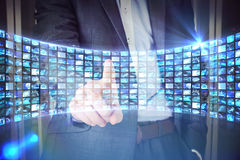 Composite image of businessman in grey suit pointing. Businessman in grey suit pointing against curve of digital screens in blue Royalty Free Stock Image