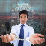 Composite image of businessman with handcuffs Royalty Free Stock Images