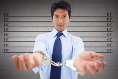 Composite image of businessman with handcuffs Stock Image