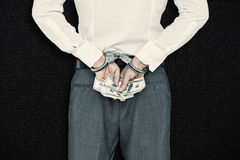 Composite image of businessman in handcuffs holding bribe Royalty Free Stock Photo