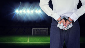 Composite image of businessman in handcuffs holding bribe Royalty Free Stock Photos