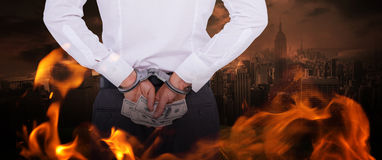 Composite image of businessman in handcuffs holding bribe Stock Image
