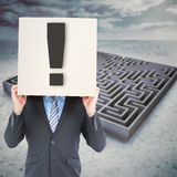Composite image of businessman hiding head with a box. Businessman hiding head with a box against big maze under cloudy sky Royalty Free Stock Photo