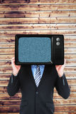 Composite image of businessman hiding head with a box Stock Images