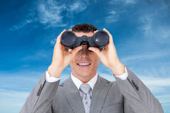 Composite image of businessman holding binoculars Royalty Free Stock Image