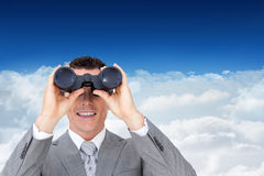 Composite image of businessman holding binoculars. Businessman holding binoculars against bright blue sky over clouds Royalty Free Stock Images