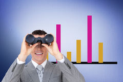 Composite image of businessman holding binoculars stock photo