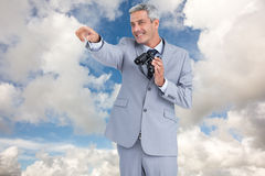 Composite image of businessman holding binoculars and pointing out something Royalty Free Stock Images