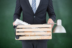 Composite image of businessman holding box of his things Royalty Free Stock Photography