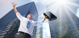 Composite image of businessman holding briefcase and cheering Royalty Free Stock Images