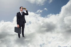 Composite image of businessman holding a briefcase while using binoculars Royalty Free Stock Images
