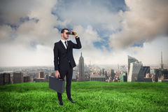 Composite image of businessman holding a briefcase while using binoculars Royalty Free Stock Photo