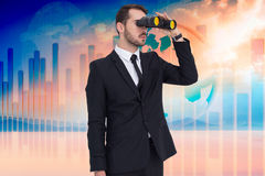 Composite image of businessman holding a briefcase while using binoculars Stock Photography