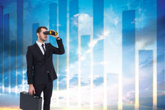 Composite image of businessman holding a briefcase while using binoculars Stock Photo