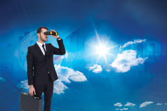 Composite image of businessman holding a briefcase while using binoculars Stock Images
