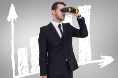Composite image of businessman holding a briefcase while using binoculars Royalty Free Stock Image
