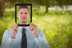 Composite image of businessman holding digital tablet in front of face Royalty Free Stock Image