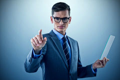 Composite image of businessman holding glass sheet and touching invisible screen Royalty Free Stock Photos