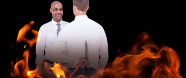 Composite image of businessman holding knife behind his back Stock Images