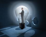 Composite image of businessman holding laptop in light bulb Royalty Free Stock Photos