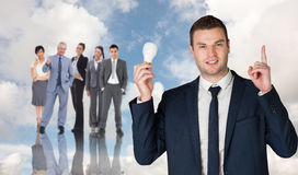 Composite image of businessman holding light bulb and pointing Royalty Free Stock Image