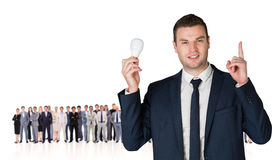 Composite image of businessman holding light bulb and pointing Royalty Free Stock Photography