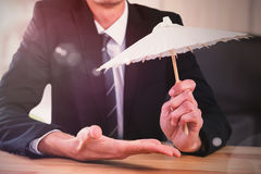 Composite image of businessman holding paper umbrella Royalty Free Stock Photos