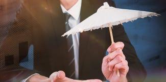 Composite image of businessman holding paper umbrella. Businessman holding paper umbrella against blue background Stock Image