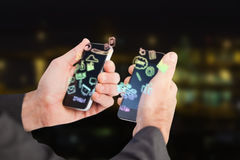 Composite image of businessman holding a phone in each hand 3d. Businessman holding a phone in each hand against illuminated city by lake 3d Royalty Free Stock Photography