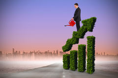 Composite image of businessman holding red watering can. Businessman holding red watering can against road leading out to the horizon Royalty Free Stock Photos