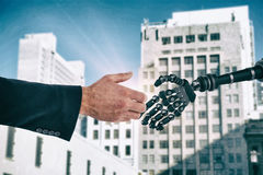 Composite image of businessman holding something with his hands. Businessman holding something with his hands against low angle view of city buildings Royalty Free Stock Photo