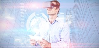 Composite image of businessman holding tablet while wearing vr glasses. Businessman holding tablet while wearing vr glasses against composite image of technology stock photos