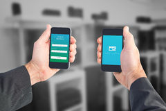 Composite image of businessman holding two smart phones Stock Image
