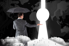 Composite image of businessman holding an umbrella with hand out Stock Images